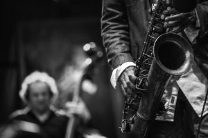 A black and white shot of a man playing jazz on a saxophone