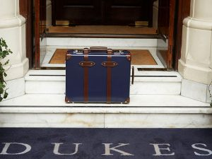 A blue, traditional suitcase outside of DUKES London in Mayfair